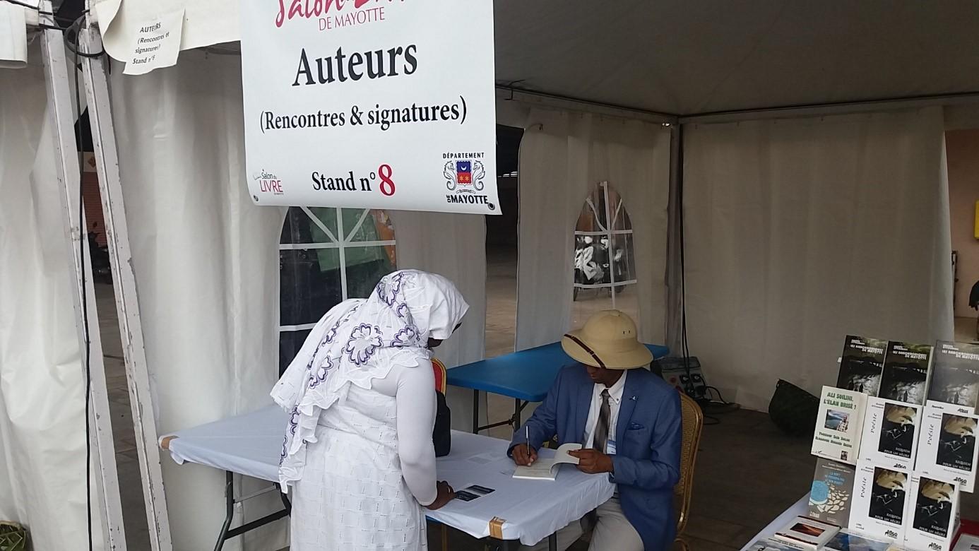Nassur Attoumani signant ses ouvrages au salon du livre de Mayotte en septembre 2017 © R. A. Tchokothe